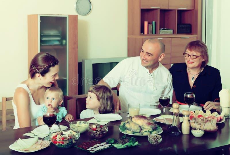 Gelukkige drie generatiesfamilie over eettafel thuis stock afbeelding