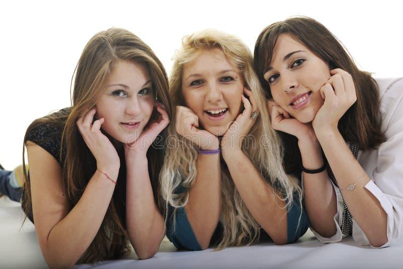 Gelukkige drie jonge meisjes die op wit worden geïsoleerdl royalty-vrije stock afbeeldingen