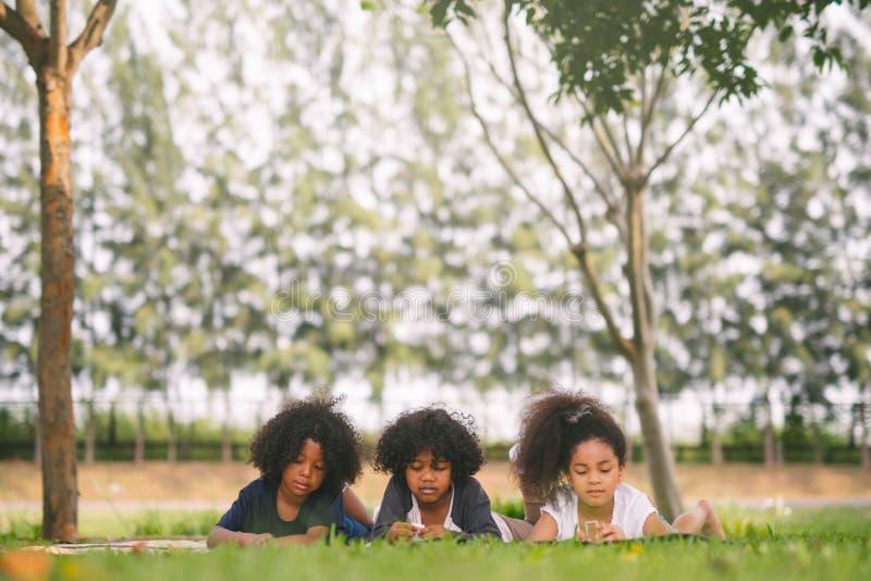 Gelukkige drie kleine vrienden die op het gras in het park leggen Amerikaanse Afrikaanse kinderen die stuk speelgoed in park spel stock foto's
