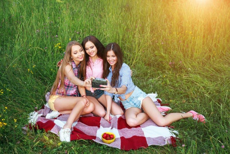 Gelukkige drie vriendenvrouwen een selfie op een de zomersdag in park royalty-vrije stock foto