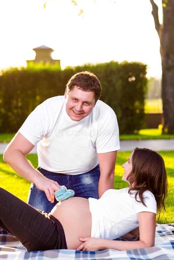 Gelukkige echtgenoot met het zwangere vrouw spelen in aard stock foto