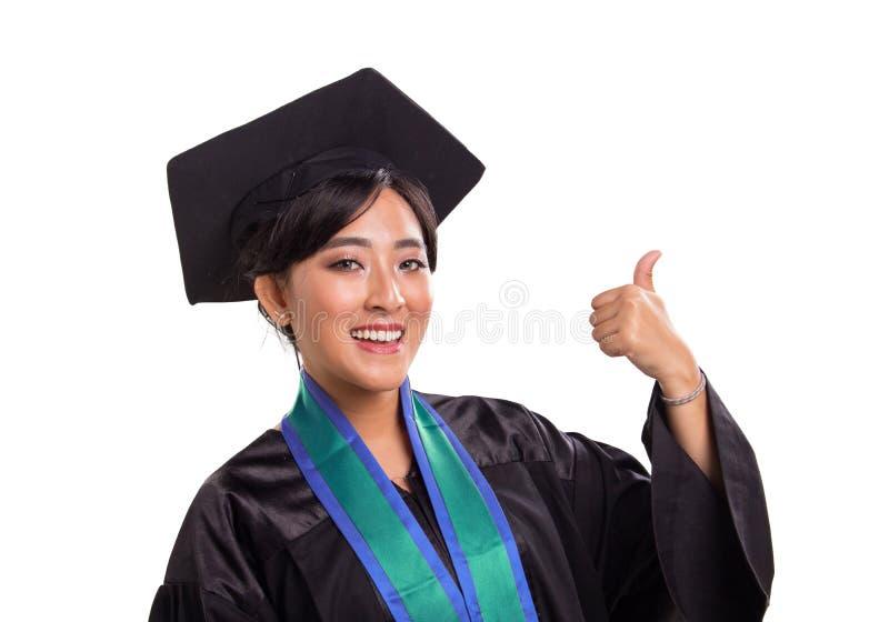 Gelukkige een diploma behalende Aziatische student die duim opgeven royalty-vrije stock afbeelding