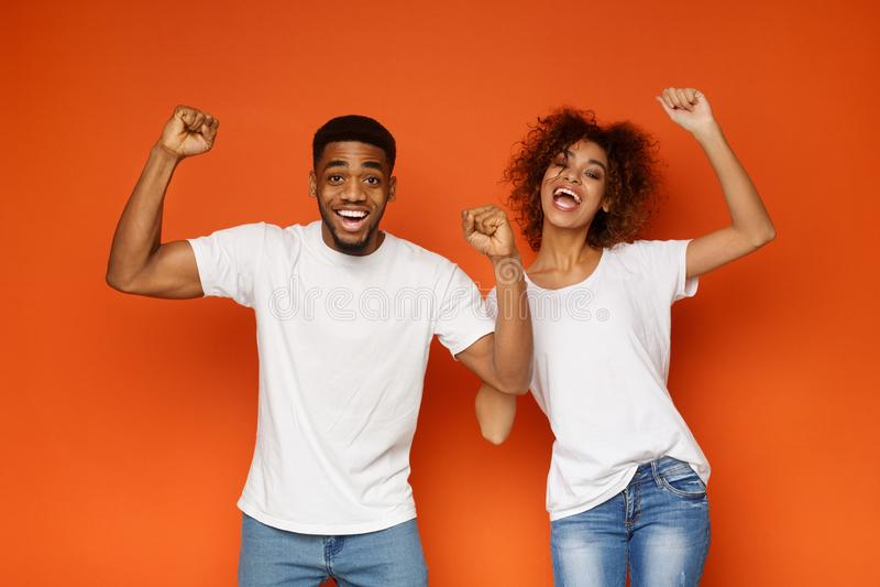 Gelukkige emotionele zwarte man en vrouw die van succes samen genieten royalty-vrije stock foto's