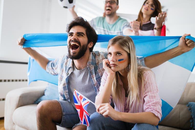Gelukkige en droevige vrienden of voetbalventilators die voetbal op spel letten stock afbeelding