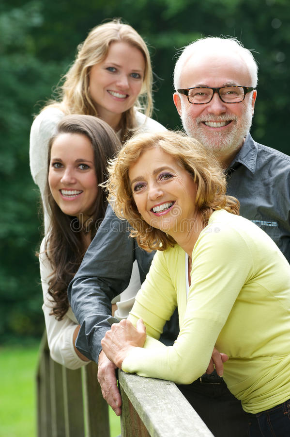 Gelukkige en familie zich in openlucht glimlachen die verenigen royalty-vrije stock foto's