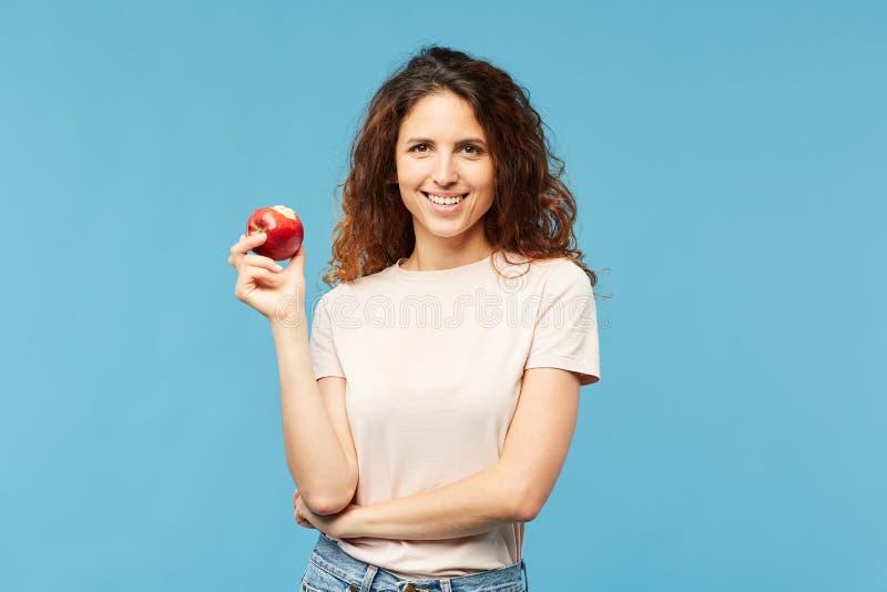 Gelukkige en gezonde jonge donkerbruine vrouw met rode rijpe appel stock foto's