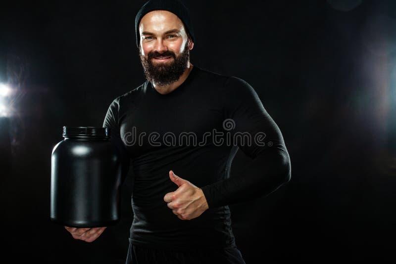 Gelukkige en gezonde spier jonge fitness sportenmens met een kruik sportenvoeding - proteïne, gainer en caseïne royalty-vrije stock fotografie