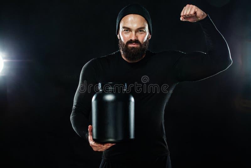 Gelukkige en gezonde spier jonge fitness sportenmens met een kruik sportenvoeding - proteïne, gainer en caseïne royalty-vrije stock foto's