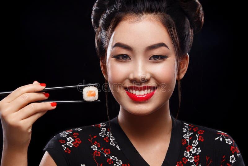 Gelukkige en glimlachende Aziatische vrouw die sushi en broodjes op een zwarte achtergrond eten royalty-vrije stock foto's