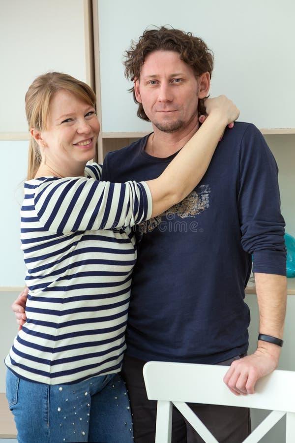 Gelukkige en glimlachende blonde vrouw die haar kalme echtgenoot omhelzen, binnen stock afbeelding