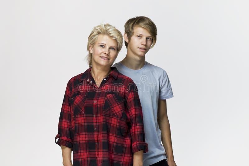Gelukkige en glimlachende moeder en zoon Het houden van familieportret tegen witte achtergrond stock afbeelding