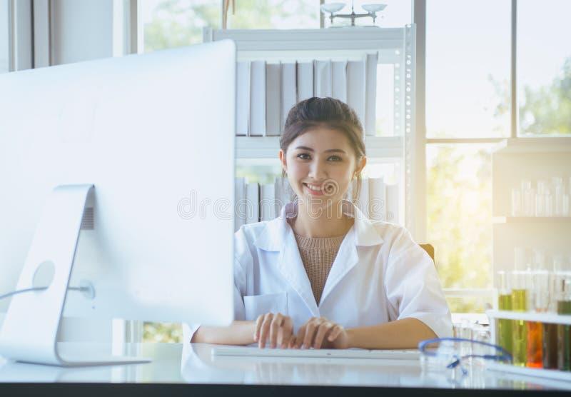 Gelukkige en glimlachende wetenschapper Aziatische vrouwen die en computertoetsenbord werken gebruiken op bureau in bureauruimte, royalty-vrije stock foto's