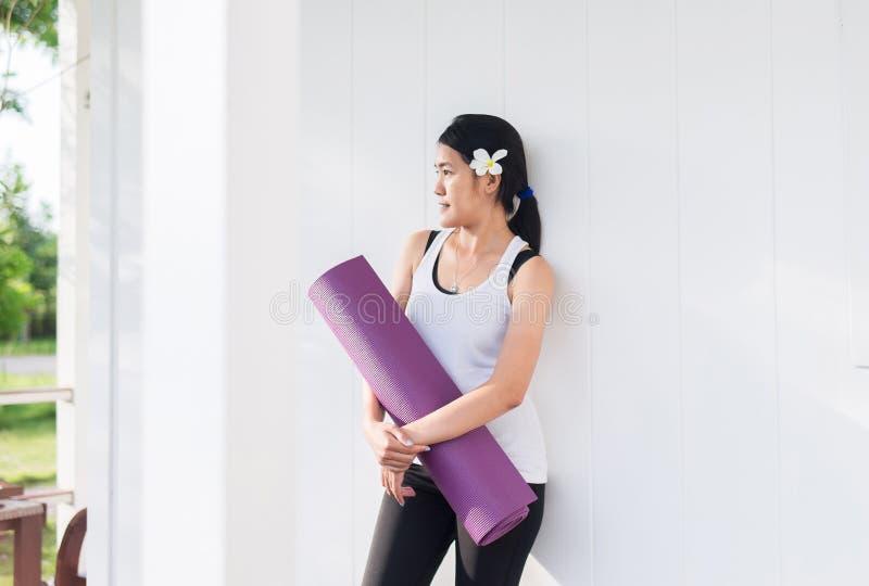 Gelukkige en het glimlachen Aziatische vrouwenhanden die yogamat na een training, een Oefeningsmateriaal, een Gezond fitness en e royalty-vrije stock foto