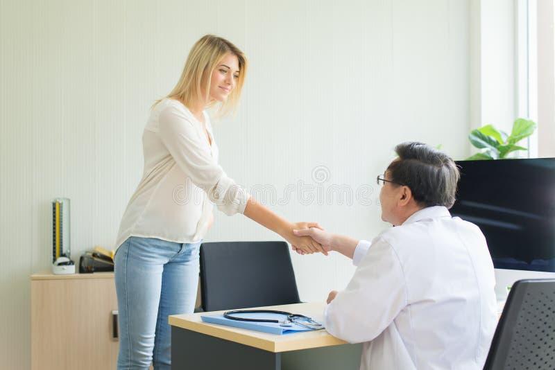Gelukkige en het glimlachen vrouwen geduldige gevende handdruk aan man arts bij het ziekenhuis royalty-vrije stock fotografie