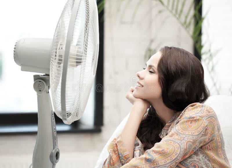 Gelukkige en het glimlachen vrouwenzitting dichtbij ventilator stock afbeeldingen