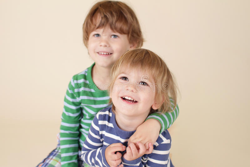 Gelukkige en Jonge geitjes die koesteren glimlachen stock foto's