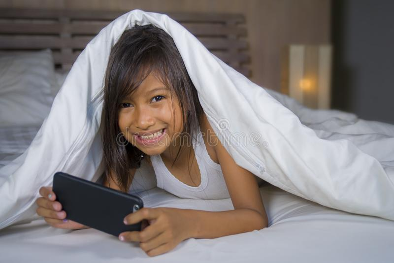 Gelukkige en mooie 7 jaar oud kind die pret hebben die Internet-spel die met mobiele telefoon spelen op binnen vrolijk en opgewek stock fotografie