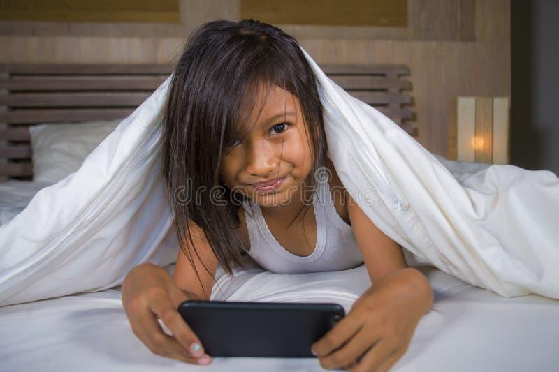 Gelukkige en mooie 7 jaar oud kind die pret hebben die Internet-spel die met mobiele telefoon spelen op binnen vrolijk en opgewek royalty-vrije stock afbeelding