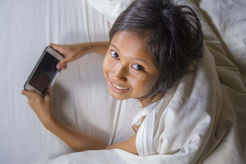 Gelukkige en mooie 7 jaar oud kind die pret hebben die Internet-spel die met mobiele telefoon spelen op binnen vrolijk en opgewek stock afbeeldingen