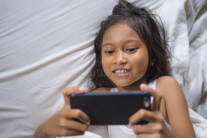 Gelukkige en mooie 7 jaar oud kind die pret hebben die Internet-spel die met mobiele telefoon spelen op binnen vrolijk en opgewek royalty-vrije stock fotografie