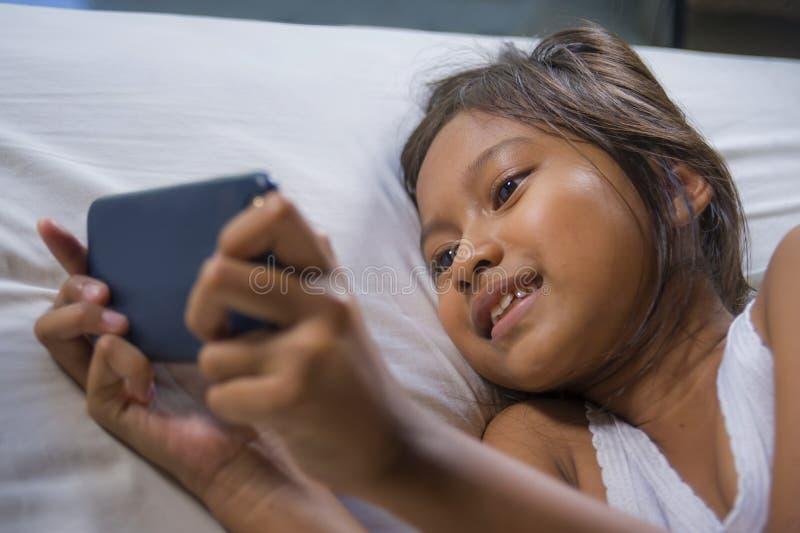Gelukkige en mooie 7 jaar oud kind die pret hebben die Internet-spel die met mobiele telefoon spelen op binnen vrolijk en opgewek stock afbeelding