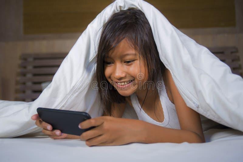 Gelukkige en mooie 7 jaar oud kind die pret hebben die Internet-spel die met mobiele telefoon spelen op vrolijk en opgewekt bed i stock foto