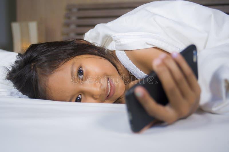 Gelukkige en mooie 7 jaar oud kind die pret hebben die Internet-spel die met mobiele telefoon spelen op vrolijk en opgewekt bed i stock foto's