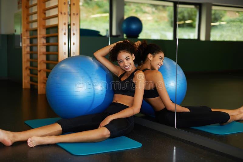 gelukkige en mooie jonge vrouwenzitting in gymnastiek met geschikte bal royalty-vrije stock afbeelding