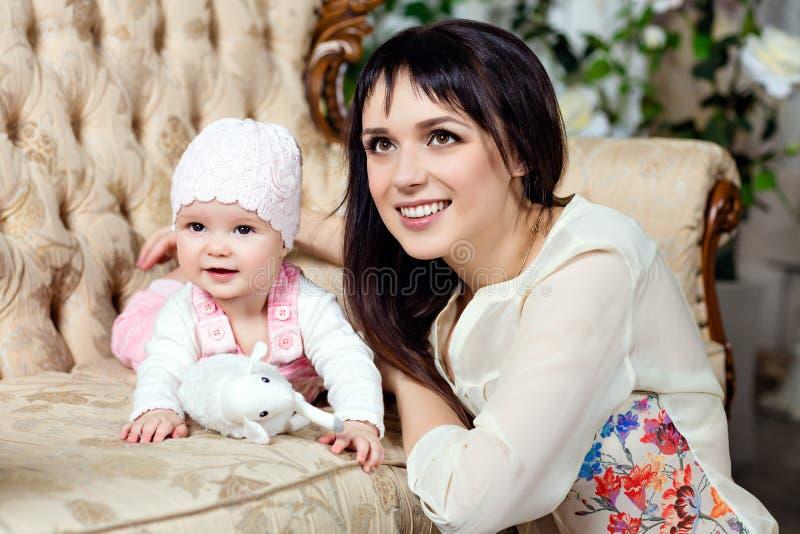 Gelukkige en mooie mamma donkerbruine grote omhelzingen die weinig daught charmeren stock fotografie