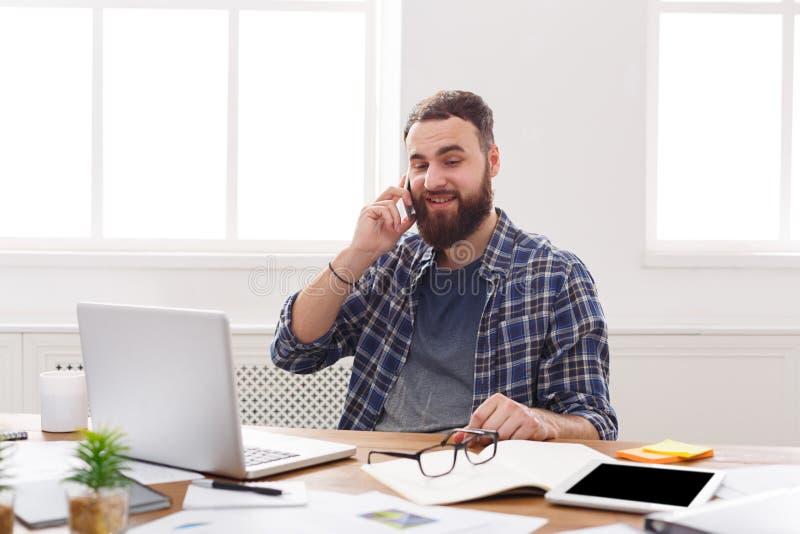 Gelukkige en ontspannen zakenmanbespreking mobiel in bureau royalty-vrije stock afbeeldingen