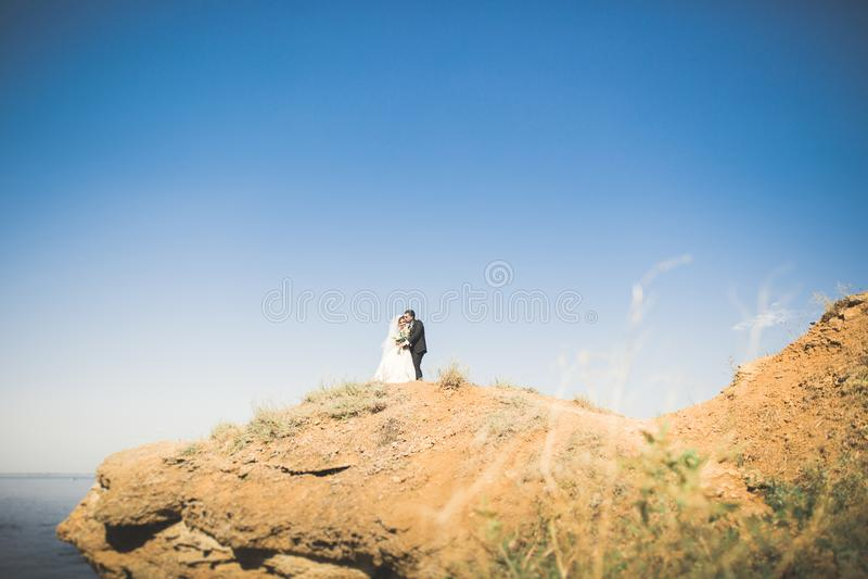 Gelukkige en romantische scène van enkel het gehuwde jonge huwelijkspaar stellen op mooi strand stock foto's
