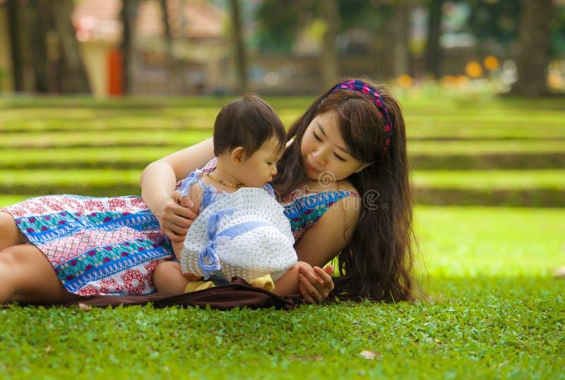 Gelukkige en speelse Aziatische Chinese vrouw als het houden van van moeder die van met zoete en mooie het meisjeszitting van de  stock fotografie