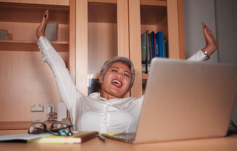 Gelukkige en succesvolle aantrekkelijke midden oude Aziatische vrouw die bij bureaulaptop opgewekt computerbureau en het vrolijke royalty-vrije stock afbeelding