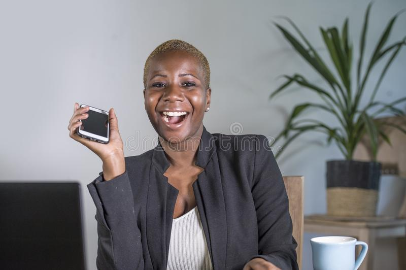Gelukkige en succesvolle zwarte afro Amerikaanse bedrijfsvrouw die op modern kantoor met het mobiele telefoon vrolijk stellen wer stock foto's