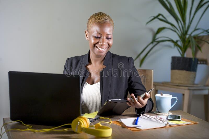 Gelukkige en succesvolle zwarte afro Amerikaanse bedrijfsvrouw die op modern kantoor werken die vrolijk gebruikend digitaal table royalty-vrije stock fotografie