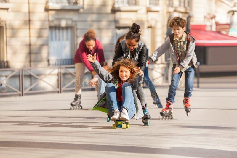 Gelukkige en tienerjaren die rollerblading met een skateboard rijden stock fotografie