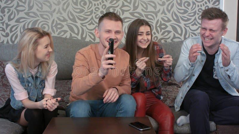 Gelukkige en toevallige groep jonge vrienden, die uit thuis samen, aan muziek via een televisie luisteren hangen die royalty-vrije stock afbeelding