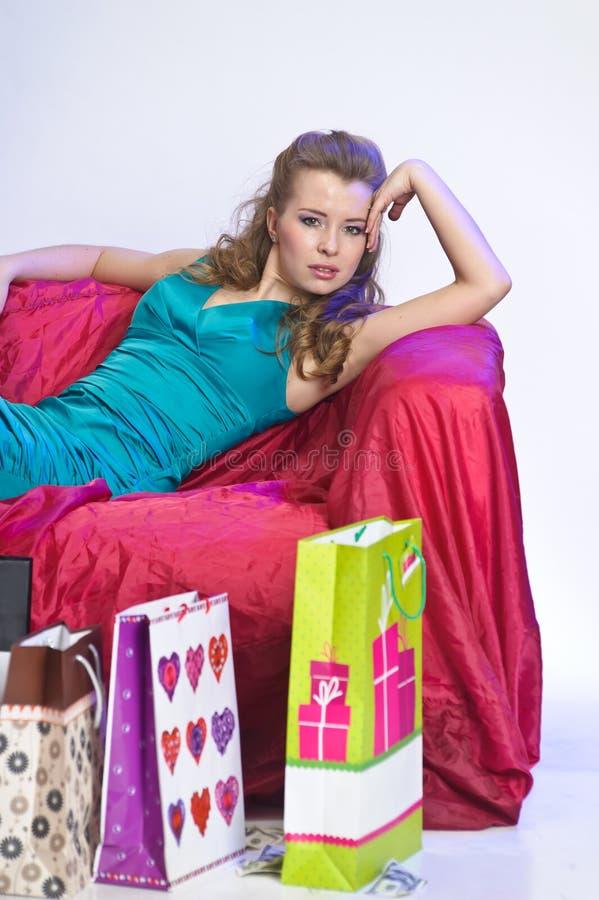 Gelukkige en vermoeide vrouw die na het winkelen rusten stock foto