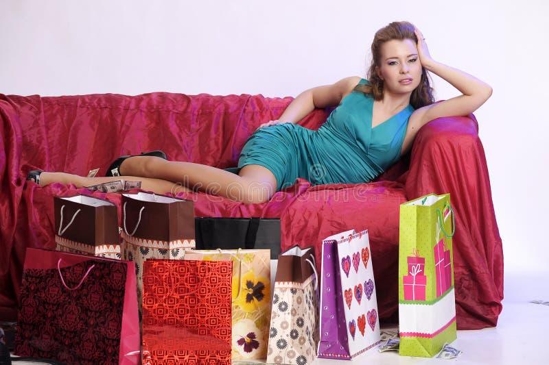 Gelukkige en vermoeide vrouw die na het winkelen rusten royalty-vrije stock afbeeldingen
