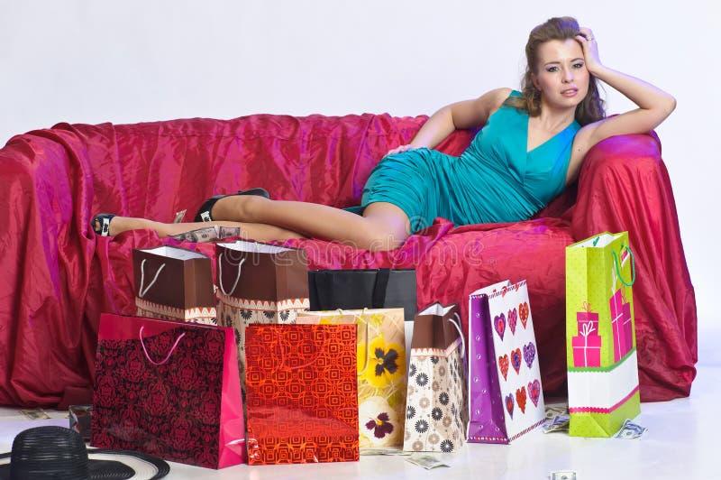 Gelukkige en vermoeide vrouw die na het winkelen rusten stock foto's