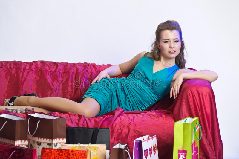 Gelukkige en vermoeide vrouw die na het winkelen rusten stock afbeeldingen