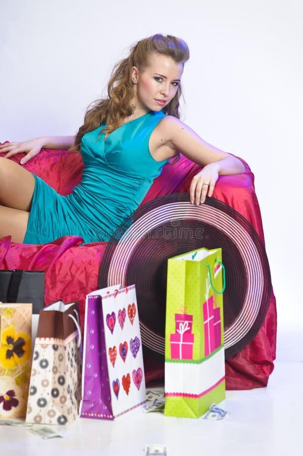Gelukkige en vermoeide vrouw die na het winkelen rusten stock afbeelding