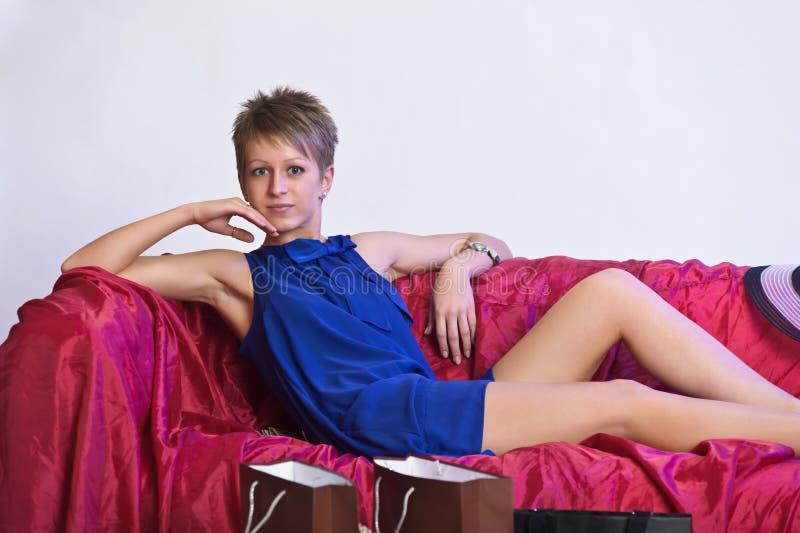 Gelukkige en vermoeide vrouw die na het winkelen rusten royalty-vrije stock fotografie
