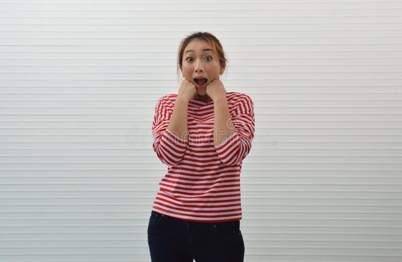 Gelukkige en verraste jonge Aziatische vrouw rood en wit gestript overhemd dragen en jeans die handen op haar wangen over witte m royalty-vrije stock foto