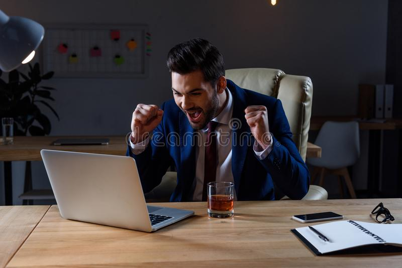 gelukkige en verraste zakenman die laptop en het tonen bekijken royalty-vrije stock fotografie