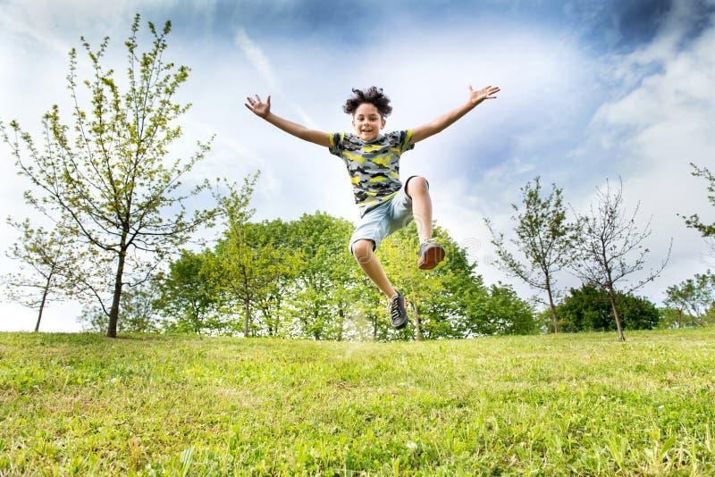 Gelukkige energieke jonge jongen die hoog in de lucht springen royalty-vrije stock foto
