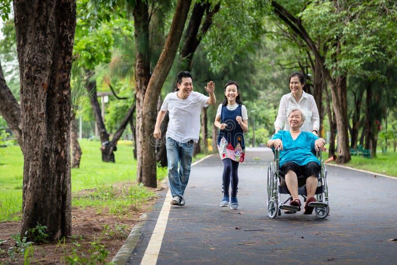 Gelukkige familie, Aziaat weinig kindmeisje of dochter speelmarkeringsspel, lopen blij met vader, bejaard in rolstoel, moeder en royalty-vrije stock fotografie