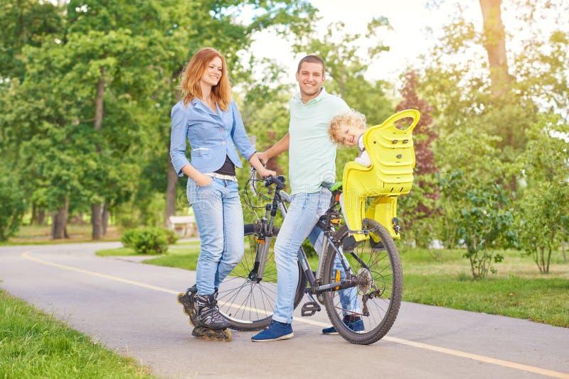 Gelukkige familie berijdende fiets bij het park royalty-vrije stock fotografie