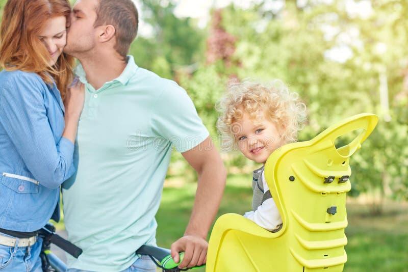 Gelukkige familie berijdende fiets bij het park stock foto