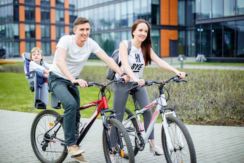 Gelukkige familie berijdende fietsen in de stad stock fotografie